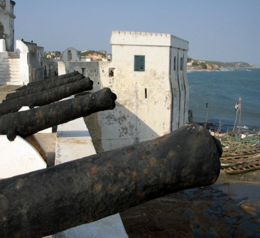 Old cannons at Cape Coast Castle overlook fishing boats